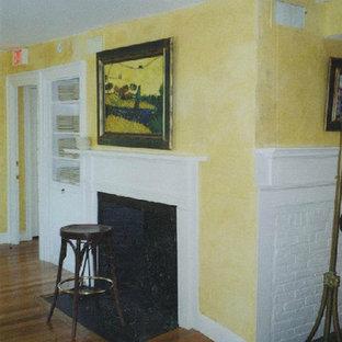 Idee per un soggiorno tradizionale con pareti gialle, pavimento in legno massello medio e camino classico