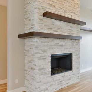 Idee per un grande soggiorno design aperto con pareti grigie, parquet chiaro, camino classico, cornice del camino in pietra, nessuna TV e pavimento beige