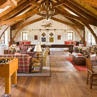 Esempio di un soggiorno stile rurale aperto con sala giochi, pavimento in legno massello medio, camino classico, TV autoportante e cornice del camino in pietra