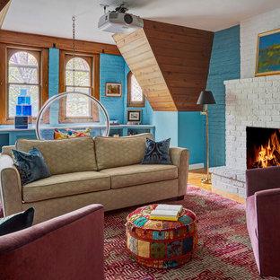 シカゴのエクレクティックスタイルのおしゃれなファミリールーム (青い壁、無垢フローリング、標準型暖炉、レンガの暖炉まわり、茶色い床) の写真