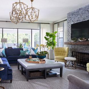 Immagine di un grande soggiorno chic aperto con pareti beige, pavimento con piastrelle in ceramica, camino classico, cornice del camino in pietra ricostruita, parete attrezzata e pavimento grigio