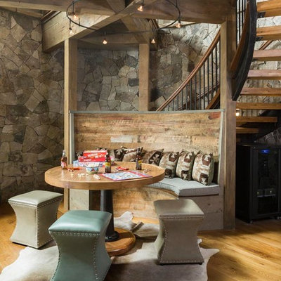 Example of a mid-sized mountain style open concept medium tone wood floor, brown floor and exposed beam family room design in Denver with gray walls