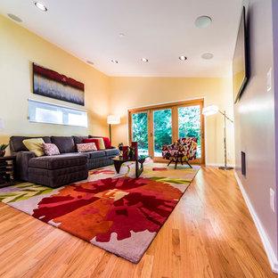 Foto di un soggiorno contemporaneo di medie dimensioni e aperto con pareti viola, parquet chiaro e TV a parete