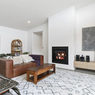 Photo of a small beach style open concept family room in Geelong with concrete floors, a standard fireplace, a plaster fireplace surround, a freestanding tv and grey floor.