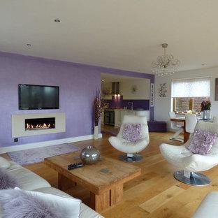 ロサンゼルスの大きいコンテンポラリースタイルのおしゃれなファミリールーム (紫の壁、淡色無垢フローリング、横長型暖炉、コンクリートの暖炉まわり、壁掛け型テレビ、茶色い床) の写真