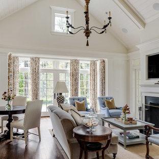 Modelo de sala de estar de estilo de casa de campo, de tamaño medio, con paredes blancas, chimenea tradicional, suelo marrón, suelo de madera oscura y pared multimedia