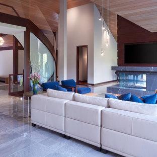 Ispirazione per un ampio soggiorno design aperto con sala della musica, pareti grigie, pavimento in gres porcellanato, camino bifacciale, cornice del camino in pietra, pavimento grigio e parete attrezzata
