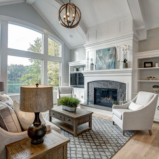 Diseño de sala de estar tradicional renovada con paredes grises, suelo de madera clara, chimenea tradicional, marco de chimenea de baldosas y/o azulejos, pared multimedia y suelo beige