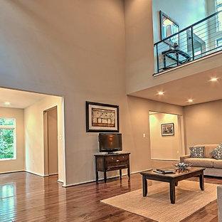 Esempio di un grande soggiorno design aperto con pareti grigie, pavimento in vinile, camino classico, cornice del camino in pietra, TV autoportante e pavimento marrone