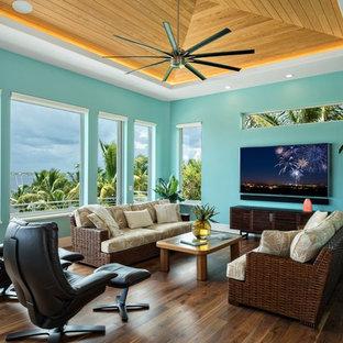 マイアミのトロピカルスタイルのおしゃれなファミリールーム (青い壁、濃色無垢フローリング、暖炉なし、壁掛け型テレビ、茶色い床) の写真