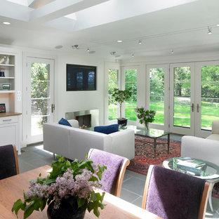 Foto di un soggiorno boho chic di medie dimensioni con pareti bianche, pavimento in ardesia, camino classico, cornice del camino in metallo e TV a parete