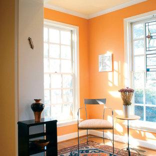 Cette photo montre une salle de séjour tendance avec un mur orange et un sol en bois brun.
