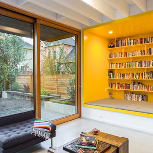 Example of a trendy open concept concrete floor and gray floor family room design in Portland with white walls