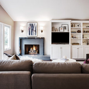 This is an example of a large contemporary open plan family and games room in San Francisco with a standard fireplace, a built-in media unit, a stone fireplace surround, grey walls and brown floors.