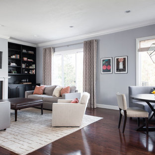 Example of a large trendy dark wood floor family room design in San Francisco with gray walls, a standard fireplace, a stone fireplace and a wall-mounted tv