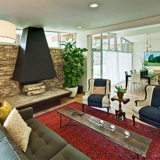 Idée de décoration pour une salle de séjour design ouverte avec un mur beige, cheminée suspendue et un manteau de cheminée en pierre.