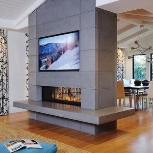 トロントの中くらいのコンテンポラリースタイルのおしゃれなファミリールーム (白い壁、無垢フローリング、コンクリートの暖炉まわり、埋込式メディアウォール) の写真