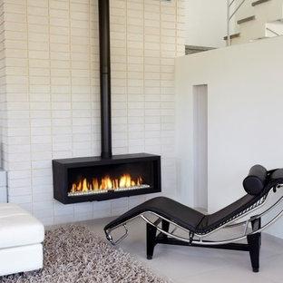 トロントの中サイズのコンテンポラリースタイルのおしゃれなファミリールーム (白い壁、磁器タイルの床、吊り下げ式暖炉、レンガの暖炉まわり) の写真
