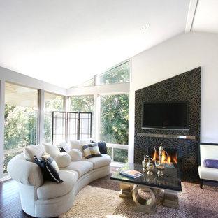 Ejemplo de sala de estar abierta, actual, extra grande, con marco de chimenea de baldosas y/o azulejos, suelo de madera en tonos medios, chimenea tradicional, televisor colgado en la pared y paredes blancas