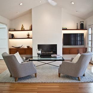 サンフランシスコの中サイズのコンテンポラリースタイルのおしゃれなファミリールーム (白い壁、淡色無垢フローリング、横長型暖炉、漆喰の暖炉まわり、壁掛け型テレビ、茶色い床) の写真