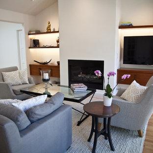 Idée de décoration pour une salle de séjour design ouverte et de taille moyenne avec un mur blanc, un sol en bois clair, une cheminée ribbon, un manteau de cheminée en plâtre, un téléviseur fixé au mur et un sol marron.