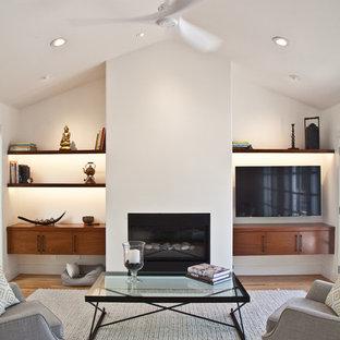 サンフランシスコの中サイズのコンテンポラリースタイルのおしゃれなファミリールーム (白い壁、淡色無垢フローリング、横長型暖炉、漆喰の暖炉まわり、壁掛け型テレビ、ミュージックルーム) の写真