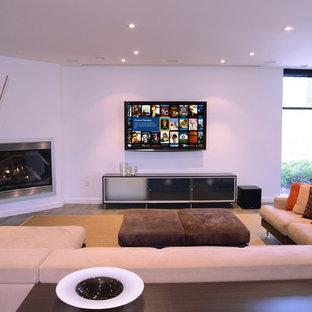 Esempio di un grande soggiorno minimal con pareti bianche, camino ad angolo, TV a parete e cornice del camino in metallo