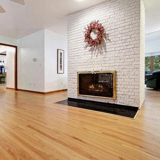 ニューヨークの巨大なコンテンポラリースタイルのおしゃれなファミリールーム (白い壁、無垢フローリング、両方向型暖炉、レンガの暖炉まわり) の写真