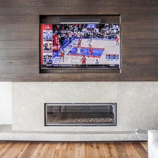 アトランタの広いビーチスタイルのおしゃれな独立型ファミリールーム (壁掛け型テレビ、白い壁、淡色無垢フローリング、横長型暖炉、コンクリートの暖炉まわり、茶色い床) の写真