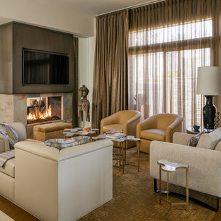 Inspiration for a mid-sized contemporary travertine floor and beige floor family room remodel in Other with a two-sided fireplace, a stone fireplace, a wall-mounted tv and beige walls