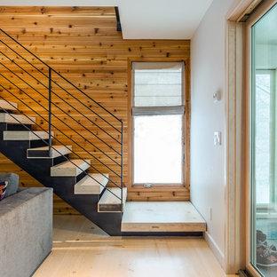 Cette photo montre une grande salle de séjour tendance ouverte avec un mur blanc, un sol en bois clair, cheminée suspendue et un téléviseur fixé au mur.