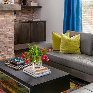 アトランタの大きいコンテンポラリースタイルのおしゃれなファミリールーム (ホームバー、グレーの壁、無垢フローリング、標準型暖炉、レンガの暖炉まわり、壁掛け型テレビ) の写真