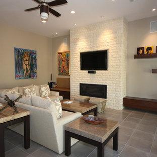 ラスベガスの中サイズのコンテンポラリースタイルのおしゃれなファミリールーム (ベージュの壁、磁器タイルの床、吊り下げ式暖炉、レンガの暖炉まわり、壁掛け型テレビ、グレーの床) の写真