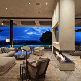 Esempio di un ampio soggiorno moderno aperto con pareti beige, pavimento in pietra calcarea, camino bifacciale e cornice del camino in intonaco