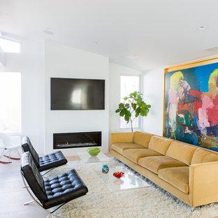 Idée de décoration pour une salle de séjour marine avec un mur blanc, un sol en bois clair, une cheminée ribbon, un téléviseur fixé au mur et un sol beige.