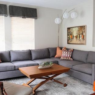 Ejemplo de sala de estar abierta, actual, pequeña, sin chimenea, con paredes grises, suelo de madera en tonos medios y televisor colgado en la pared