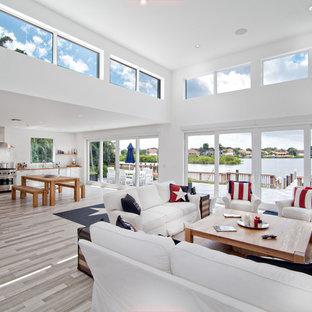 Immagine di un soggiorno costiero aperto con pareti bianche, pavimento in legno massello medio, nessuna TV, nessun camino e pavimento beige