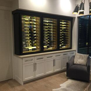 Imagen de sala de estar con barra de bar cerrada, actual, pequeña, sin chimenea, con paredes blancas, suelo de madera clara y pared multimedia