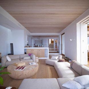 Exemple d'une salle de séjour exotique ouverte avec un mur blanc et un sol en bois clair.
