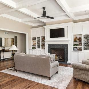 シカゴの大きいトラディショナルスタイルのおしゃれなファミリールーム (ベージュの壁、濃色無垢フローリング、標準型暖炉、木材の暖炉まわり、埋込式メディアウォール、茶色い床) の写真