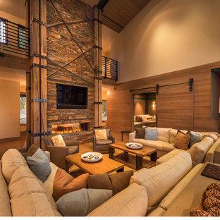 サクラメントの中サイズのコンテンポラリースタイルのおしゃれなファミリールーム (ベージュの壁、無垢フローリング、横長型暖炉、石材の暖炉まわり、埋込式メディアウォール) の写真
