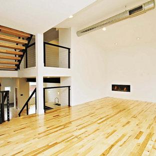Foto di un soggiorno minimal di medie dimensioni e stile loft con pareti bianche, parquet chiaro, camino lineare Ribbon e TV a parete