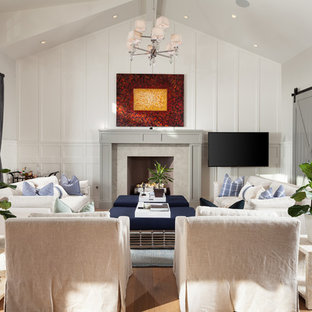 Family room - beach style light wood floor family room idea in Orange County with white walls, a standard fireplace and a wall-mounted tv