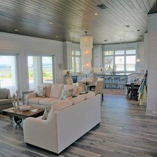 Réalisation d'une très grande salle de séjour ethnique ouverte avec un mur blanc et un sol en bois clair.