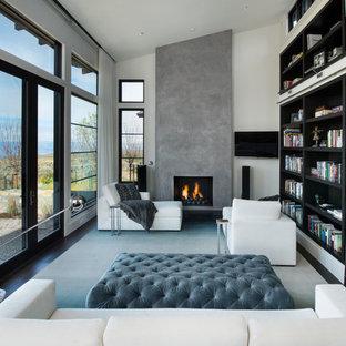 Immagine di un soggiorno minimal di medie dimensioni e aperto con libreria, pareti bianche, camino classico, cornice del camino in cemento, TV a parete, parquet scuro e pavimento marrone