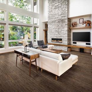 Выдающиеся фото от архитекторов и дизайнеров интерьера: большая открытая гостиная комната в современном стиле с полом из винила, белыми стенами, горизонтальным камином, фасадом камина из камня, телевизором на стене и коричневым полом
