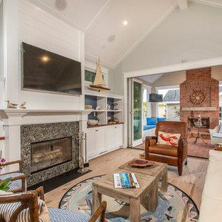 サンディエゴの中サイズのビーチスタイルのおしゃれな独立型ファミリールーム (グレーの壁、淡色無垢フローリング、標準型暖炉、石材の暖炉まわり、ベージュの床、壁掛け型テレビ) の写真