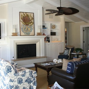 Inspiration for a mid-sized beach style open concept medium tone wood floor family room remodel in Orange County with white walls, a standard fireplace, a wood fireplace surround and a media wall