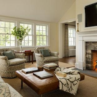 Immagine di un soggiorno classico con pareti beige, parquet scuro, camino classico, cornice del camino in pietra e TV a parete