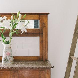 Immagine di un piccolo soggiorno country chiuso con pareti bianche, pavimento in ardesia e stufa a legna